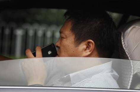A man uses his iPhone as he drives a car along a main road in central Beijing September 24, 2012. CREDIT: REUTERS/DAVID GRAY
