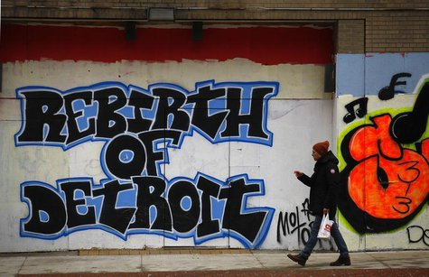 A man walks past graffiti in Detroit, Michigan, December 3, 2013. REUTERS/Joshua Lott