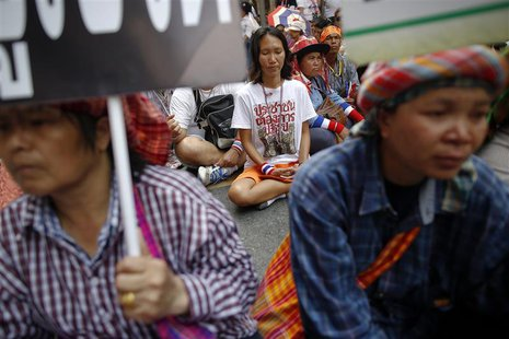 A group of anti-government protesters and some farmers sit on the main road outside the headquarters of the Royal Thai Police in central Ban