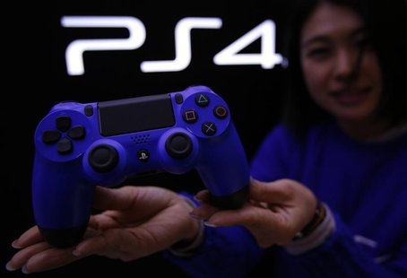 A staff at the PlayStation 4 launch event poses with PlayStation 4's game controller before its domestic launch event at the Sony Showroom i