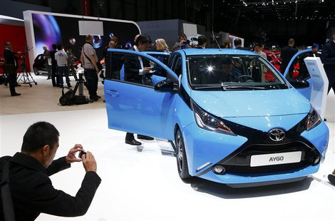 A visitor takes pictures of Toyota Aygo during the media day ahead of the 84th Geneva Motor Show at the Palexpo Arena in Geneva March 4, 201