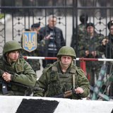Military personnel, believed to be Russian servicemen, stand outside a Ukranian military post as Ukranian servicemen look on from behind a g