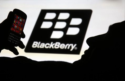 A man is silhouetted against a video screen with the Blackberry logo as he pose with a Blackberry Q10 in this photo illustration taken in th
