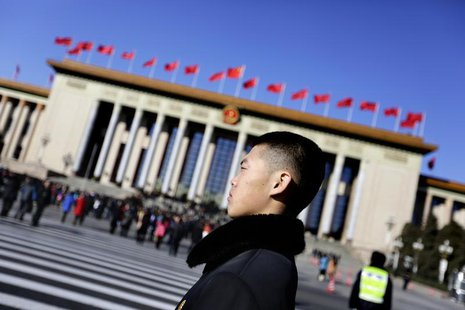 A soldier in plain clothes from the Chinese People's Liberation Army (PLA) stands guard in front of the Great Hall of the People, the venue