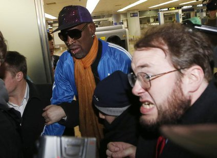 Bodyguards clear a path for former NBA basketball player Dennis Rodman (C) as journalists surround him upon his arrival from North Korea's P
