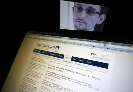 A portrait of former U.S. spy agency contractor Edward Snowden is displayed behind a screen as he answers users' questions on Twitter in thi