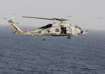 A Sikorsky SH-60 Seahawk helicopter flies near the Nimitz-class aircraft carrier USS Abraham Lincoln (CVN 72) during a transit through the S
