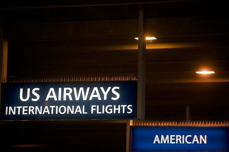 US Airways and American Airlines signs are pictured at Philadelphia International Airport in Philadelphia, Pennsylvania on December 9, 2013.