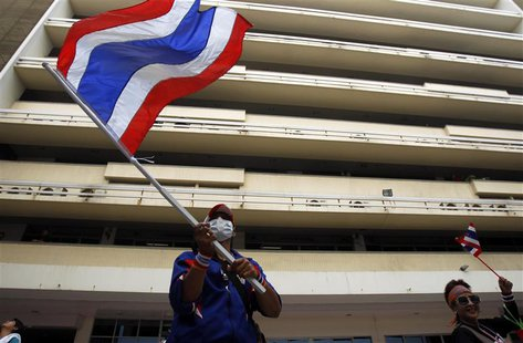 An anti-government protester waves a Thai national flag during a rally at the Department of Public Works and Town & Country Planning in Bang