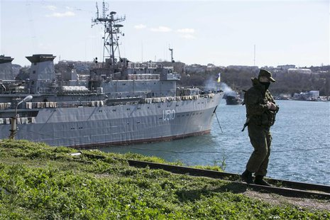 A Russian soldier stands guard near Ukrainian navy command ship Slavutych at the Crimean port of Sevastopol March 5, 2014. REUTERS/Baz Ratne