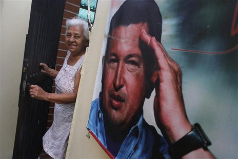 A woman smiles as she stands next to a poster of Venezuela's late President Hugo Chavez at the 23 de Enero neighbourhood in Caracas March 5,