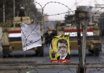 A poster of ousted Egyptian President Mohamed Mursi is pictured on barbed wires during a protest by his supporters at El-Thadiya presidentia