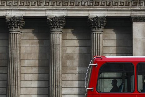 A man travels in a double-decker bus as it passes the Bank of England in central London March 24, 2010. REUTERS/Darrin Zammit Lupi