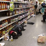 People rest at the aisle of a Publix grocery store after being stranded due to a snow storm in Atlanta, Georgia, January 29, 2014. REUTERS/T