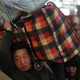 A man carries his luggage on his shoulder at a railway station in Beijing January 14, 2014. REUTERS/China Daily