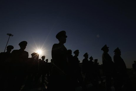 Military delegates are silhouetted as they arrive at Tiananmen Square outside the Great Hall of the People for the opening session of Nation