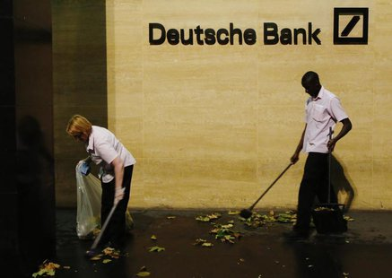 Workers sweep leaves outside Deutsche Bank offices in London December 5, 2013. REUTERS/Luke MacGregor