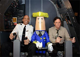 """Roger Murdock"" (Kareem Abdul-Jabbar), ""Ted Striker"" (Robert Hays) and Otto Pilot in the original ""Airplane!"" cockpit during the shoot of the new aerial ads for the Wisconsin Department of Tourism. PHOTO: Wis. Department of Tourism"