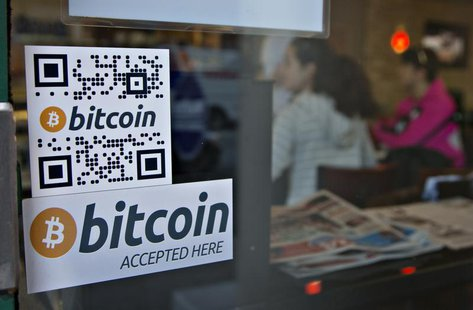 Signs on window advertise a bitcoin ATM machine that has been installed in a Waves Coffee House in Vancouver, British Columbia October 28, 2