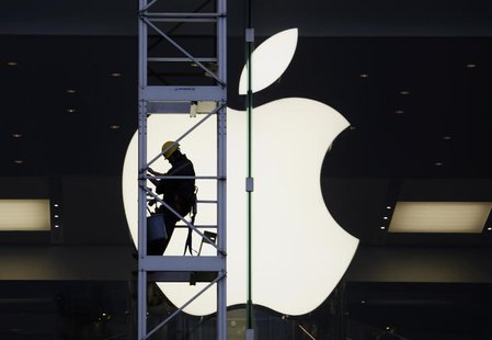 A worker climbs outside an Apple store in Hong Kong April 10, 2013. REUTERS/Bobby Yip