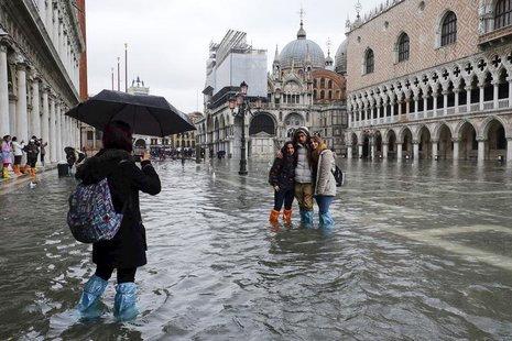 Tourists pose for a photo in a flooded St. Mark's Square during a period of seasonal high water in Venice January 31, 2014. REUTERS/Manuel S