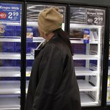A shopper passes by mostly empty refrigerator of milk at a grocery store in Lilburn, Georgia, February 12, 2014. REUTERS/Tami Chappell
