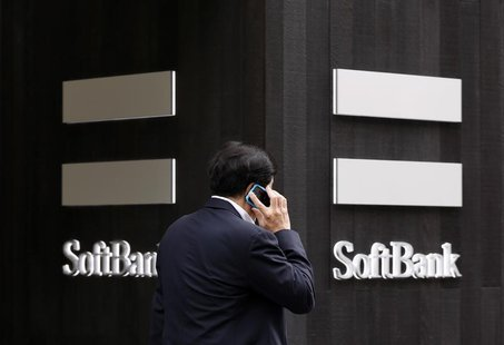 A man using a mobile phone walks past a SoftBank Corp branch in Tokyo May 29, 2013. REUTERS/Toru Hanai