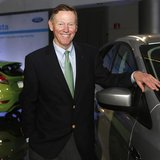 Ford Motor Co. CEO Alan Mulally poses next to a Ford vehicle during a gathering with members of the media at the Ford Conference Center in D