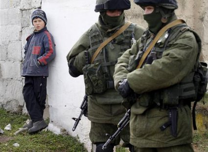 A boy looks at uniformed men, believed to be Russian servicemen, near a Ukrainian military base in the village of Perevalnoye, outside Simferopol, March 6, 2014.  CREDIT: REUTERS/VASILY FEDOSENKO