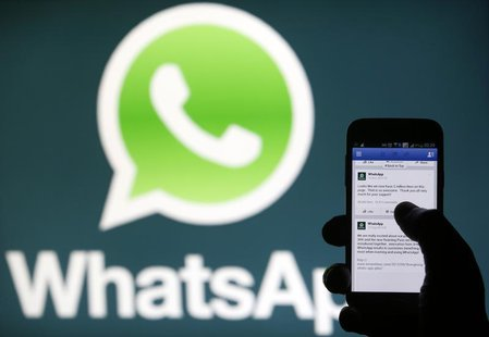 A Whatsapp App logo is seen behind a Samsung Galaxy S4 phone that is logged on to Facebook in the central Bosnian town of Zenica, February 2