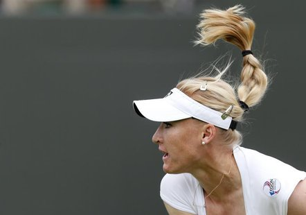 Elena Baltacha of Britain follows through on a serve to Flavia Pennetta of Italy during their women's singles tennis match at the Wimbledon