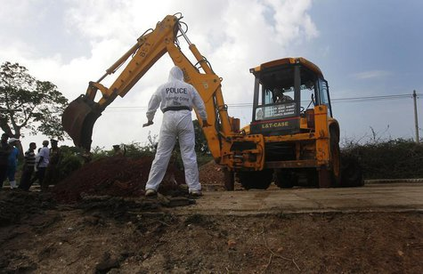 A police officer watches as an excavator digs up skeletons at a construction site in the former war zone in Mannar, about 327 km (203 miles)