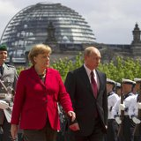 German Chancellor Angela Merkel (2nd R) and Russian President Vladimir Putin (R) inspect the honour guards before talks at the Chancellery in Berlin in this June 1, 2012 file picture. CREDIT: REUTERS/THOMAS PETER/FILES