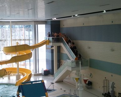 What championship high school swimming team will be taking the traditional victory slide at the Holland Community Aquatic Center this Saturday?
