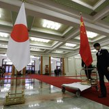 Staff from the Great Hall of the People prepare to remove Japanese (L) and Chinese national flags after a welcome ceremony for Japan's prime