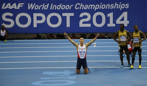 Richard Kilty of Britain celebrates victory next to Jamaicans Nesta Carter and Kimmari Roach in the men's 60 metres final at the world indoo