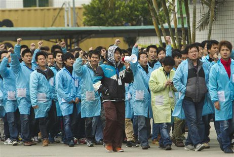 IBM workers shout slogans as they protest at an IBM factory in Shenzhen, Guangdong province, March 7, 2014. REUTERS/Alex Lee