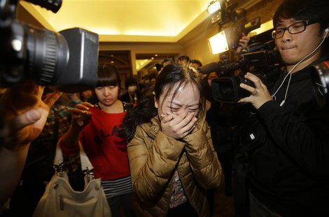 A relative (front) of a passenger of Malaysia Airlines flight MH370 cries as she walks past journalists at a hotel in Beijing March 9, 2014.