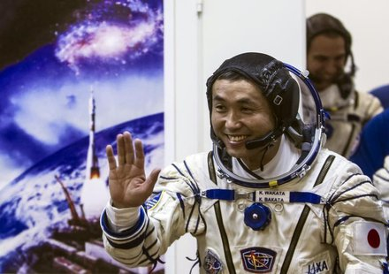 International Space Station (ISS) crew member Japanese astronaut Koichi Wakata waves after donning a space suit shortly before the blast off