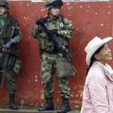 Soldiers stand guard as a woman walks past during a congressional election in Toribio in Cauca province March 9, 2014. REUTERS/Jaime Saldarr