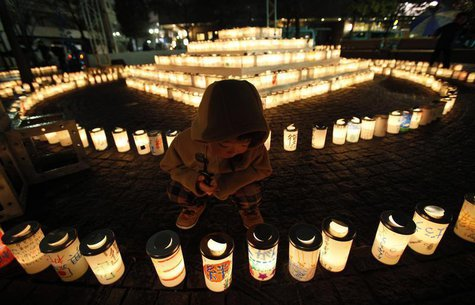 "A boy looks at a candle light with a character reading: ""bond"", written on the candle holder at a memorial held in remembrance of victims of"