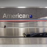A man sleeps on a conveyer belt under an American Airlines logo at John F. Kennedy International Airport in New York January 22, 2014. REUTE