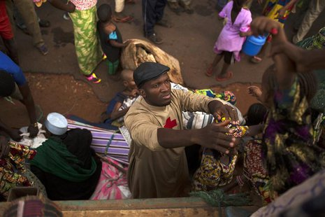 Father Bernard Kenvi (C) helps a Muslim child climb down from an open truck in the town of Bossemptele, west of Central African Republic Mar