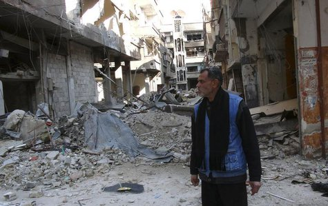 A man stands amid the rubble of damaged buildings at the Palestinian refugee camp of Yarmouk, south of Damascus February 18, 2014. REUTERS/S