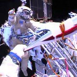 Russian astronaut Oleg Kotov holds an Olympic torch as he takes it on a spacewalk as Russian astronaut Sergei Ryazansky gives instructions o