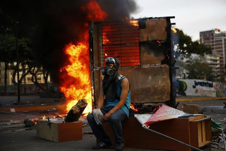 An anti-government protester sits next to a burning kiosk during a protest at Altamira square in Caracas March 9, 2014. REUTERS/Jorge Silva