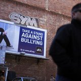 A pedestrian walks past an anti-bullying billboard in downtown Boston, Massachusetts March 3, 2011. REUTERS/Brian Snyder