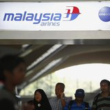 People walk under a Malaysia Airlines sign at Kuala Lumpur International Airport in Sepang March 8, 2014. REUTERS/Samsul Said