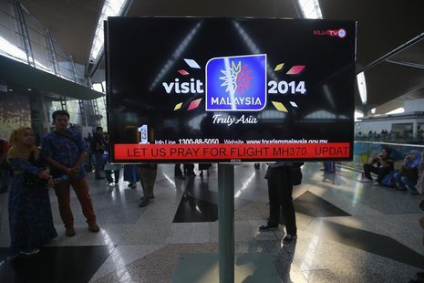 "An information screen displays a message ""Let Us Pray For Flight MH370"", regarding the missing Malaysia Airlines flight, at Kuala Lumpur Int"