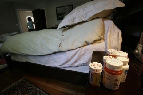 Bottle of medications sit on cancer patient Deborah Charles' bedside table at her home in Washington May 25, 2007. REUTERS/Jim Bourg